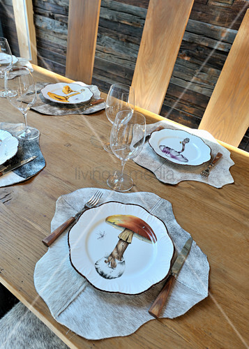 Table set with plates with mushroom motifs and animal-skin place mats