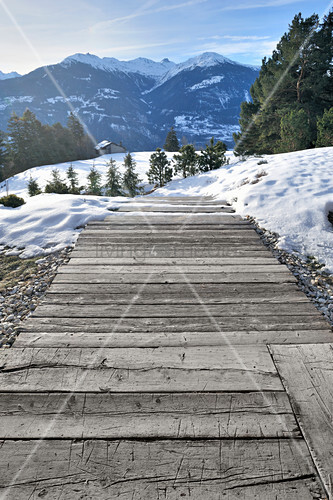 Path made from old wooden planks leading across snowy slope with mountain view
