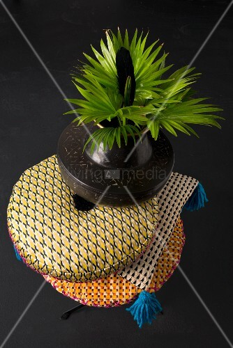 Green leaves in ethnic vase on stack of patterned cushions