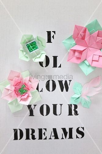 Origamiblumen auf mit Buchstaben bedrucktem Papier