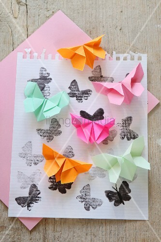 Origami butterflies on printed paper