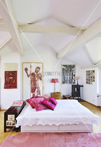Double bed with white bedspread and hot-pink cushions under wood-beamed ceiling in bedroom