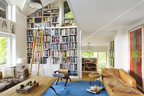 Bookcase with library ladder and leather couch in vintage-style living room