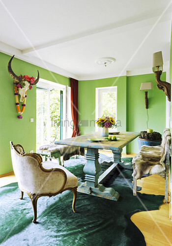 Solid wooden table, vintage benches covered with reindeer furs and velvet armchairs in green dining room with buffalo skull on wall