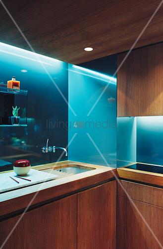 Küche aus Edelholz mit beleuchteter Rückwand