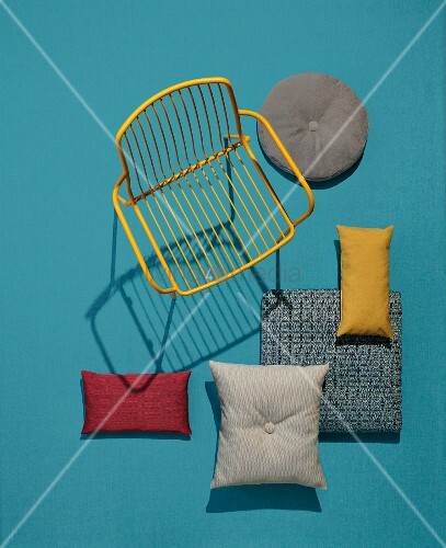 A yellow garden chair and decorative cushions made of robust outdoor fabrics