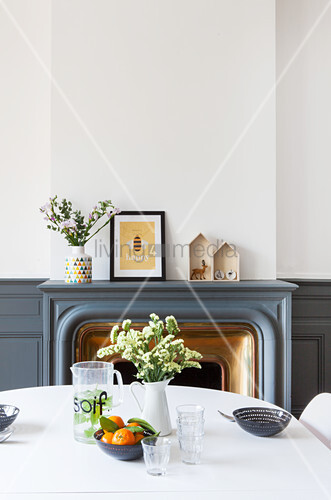 View across dining table to fireplace surrounded by dove grey wainscoting