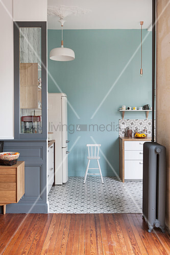 View into kitchen with pale blue wall and patterned cement floor tiles