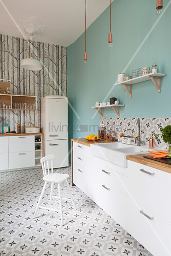 White cupboards, pale blue wall and patterned cement floor tiles in kitchen