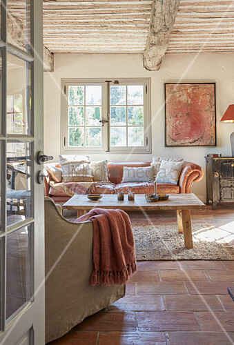 View into rustic living room with tiled floor and leather sofa