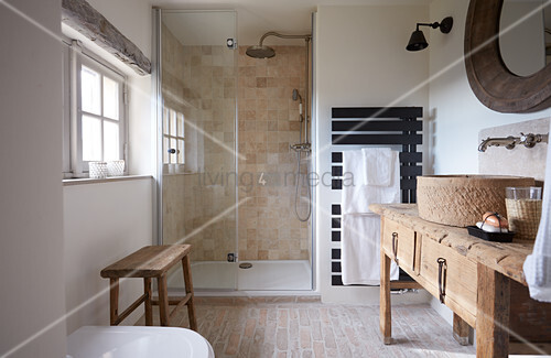 Sink on rustic wooden table in bathroom with shower area