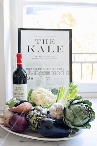 Plate of vegetables, bottle of wine and framed article in front of window