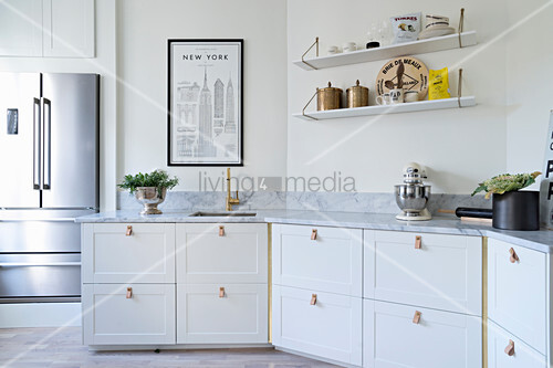Leather loops used as handles on kitchen cabinets with marble worksurface