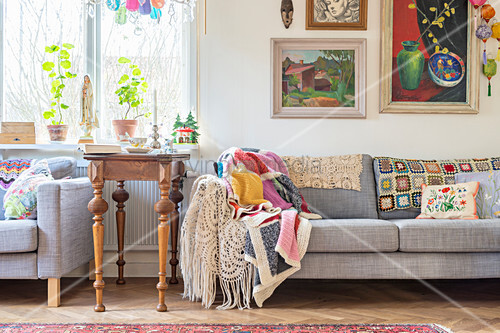 Antique side table between two sofas draped with crochet blankets
