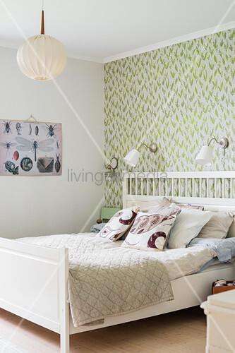 Weißes Bett Vor Grün Gemusterter Wand Im Vintage Schlafzimmer
