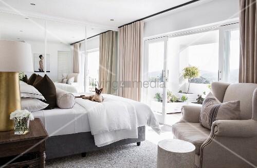 Elegant bedroom with view of summery terrace