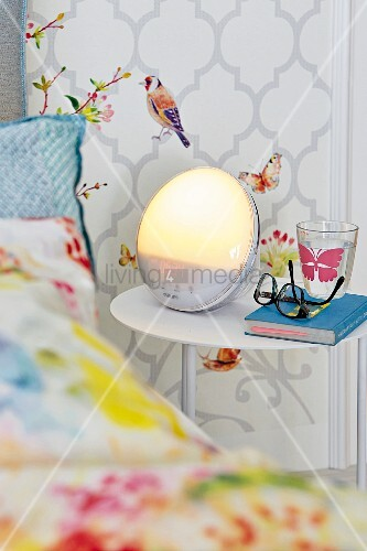 A bedside table with light alarm clock in front of a wall panel with bird wallpaper