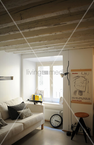 Pale sofa with scatter cushions next to window in period apartment with wood-beamed ceiling