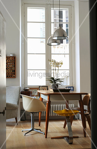 Table and various retro chairs next to lattice window in period apartment