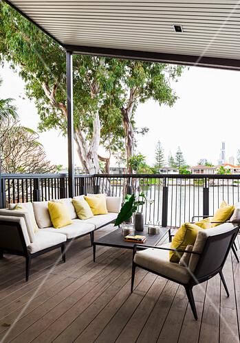 Elegante Outdoormöbel auf überdachter, erhöhter Terrasse mit Holzdeck
