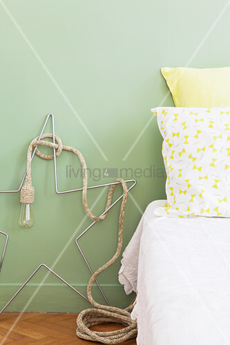 Light with crochet-covered cable draped over wire star next to bed