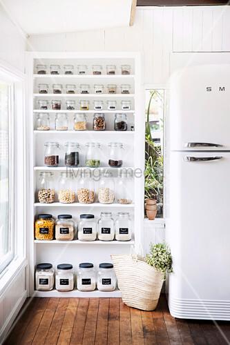 Offenes weißes Regal mit Vorratsgläsern neben Kühlschrank