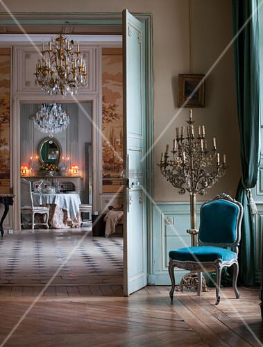 Blick durch offene Doppeltüren in Salon und auf gedeckten Esstisch