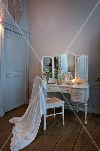 Weißer Morgenmantel über dem Stuhl vor antikem Schminkspiegel