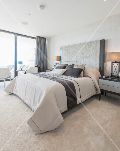 Elegant bedroom in shades of beige with glass wall