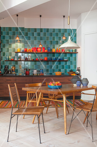 Dining table and various chairs in front of kitchen with blue wall tiles