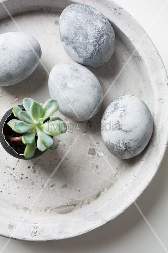 In Steinoptik bemalte Ostereier in einer Schale aus Beton