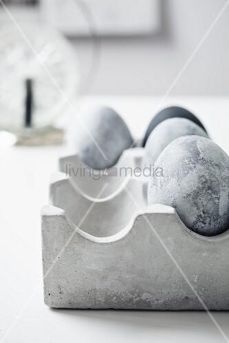 In Steinoptik bemalte Ostereier in einem Eierkarton aus Beton