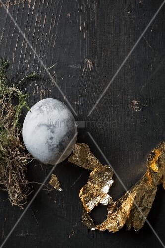 Osterei in Steinoptik mit Blattgold auf einem schwarzen Brett