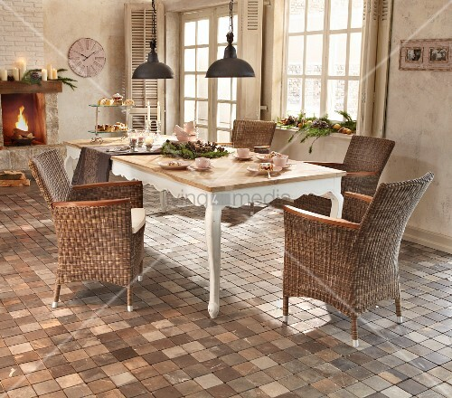 Rattan armchair, tiled floor and Advent arrangement in country-house dining area