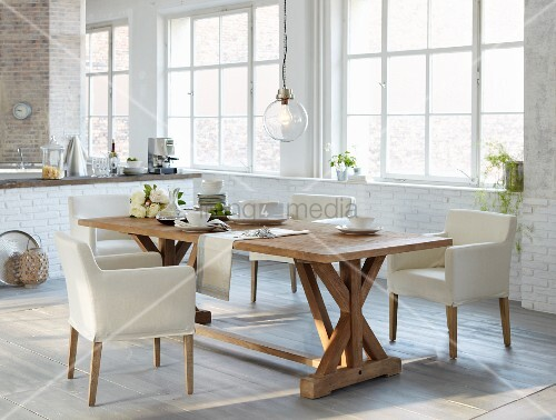 Rustic dining table and white upholstered chairs in open-plan kitchen with industrial glazing