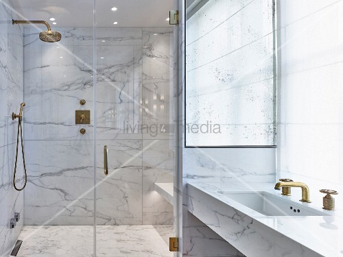 Glamorous modern bathroom with marble and gilt elements and glass doors