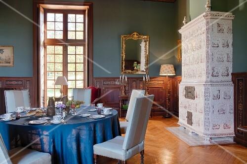 Gedeckter Tisch und Kachelofen im Chateau Des Grotteaux