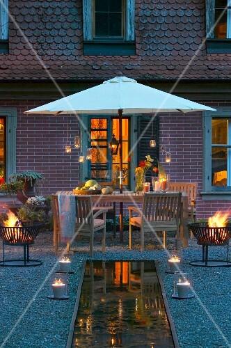 Sommerliche Abenddekoration mit Feuerschalen und Windlichtern an Wasserlauf vor Terrassenplatz