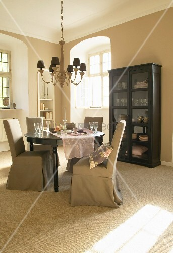 Beige loose-covered chairs and black display cabinet in elegant dining area
