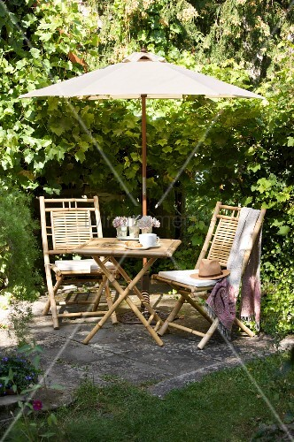 Rückzugsort im Garten mit Sonnenschirm und Bambusmöbeln
