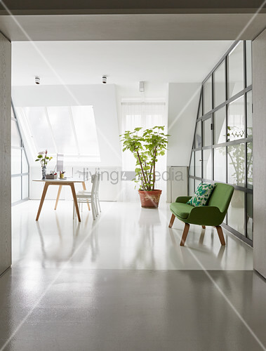 Green couch against glass wall and desk below sloping skylight
