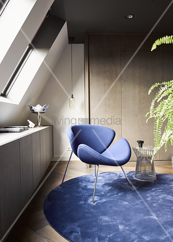 Blue designer chair on round blue rug below skylights