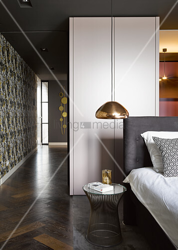 Copper-coloured ceiling lamps above bed in open-plan bedroom