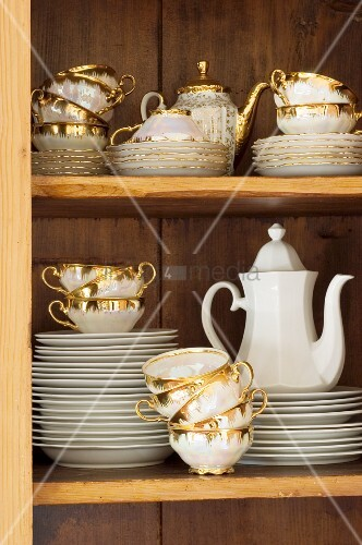 Old gold-rimmed coffee set in cupboard