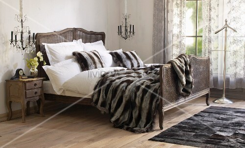 Patchwork fur rug next to French bed with fur blanket