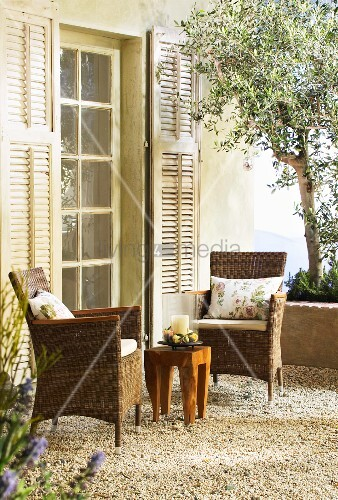 Zwei Korbstühle und ein Holztisch auf mediterraner Terrasse