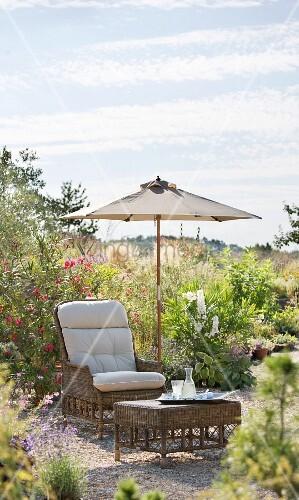 Wicker armchair and stool under parasol in summer garden