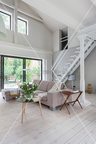 Bright, double-height living room with white floor