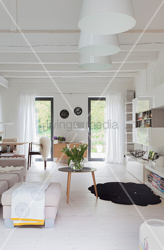 Wood Beamed Ceiling And White Floor In Bright Living Room