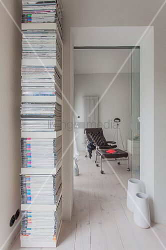 Magazines on vertical shelves next to open doorway with view of brown armchair